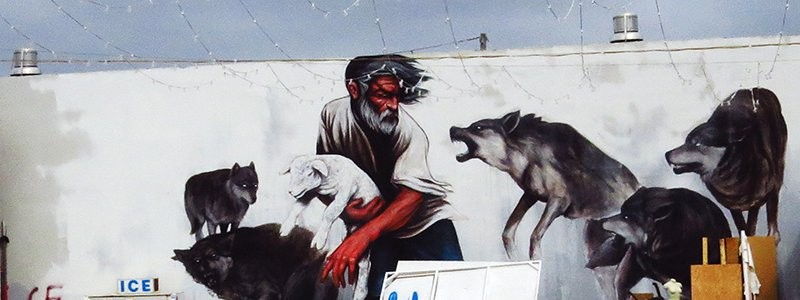 Street Art sheep protected by man from wolves