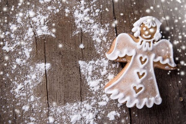 A sugar cookie angel on cutting board with powder
