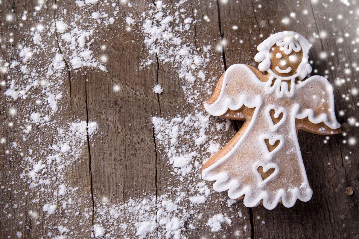 A sugar cookie angel on cutting board with powder