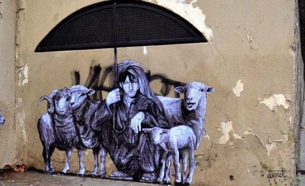 Graffiit showing shepherd covering sheep with umbrella