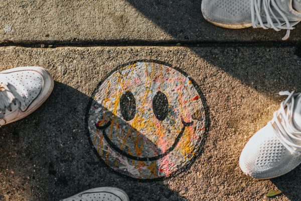 People standing around a chalk happy face drawn on ground