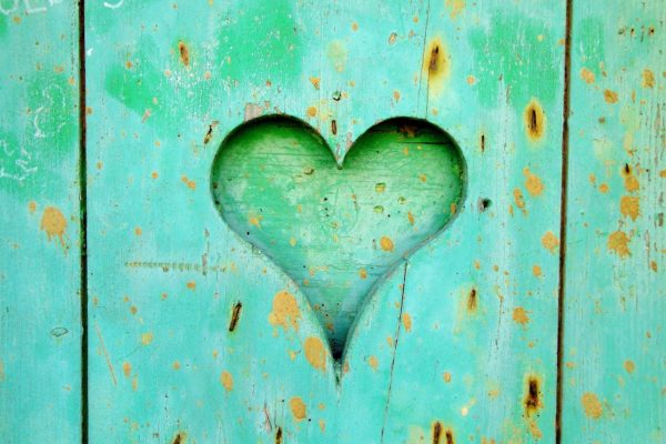 Green wooden board with heart-shaped hole